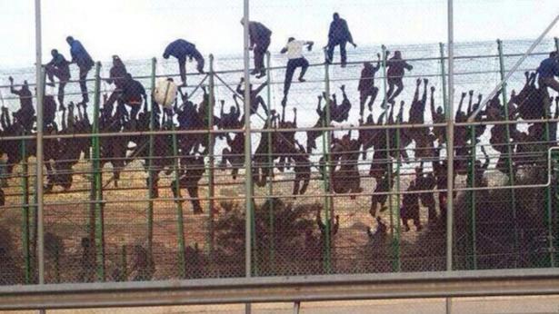 Inmigrantes tratando saltar la valla en Melilla